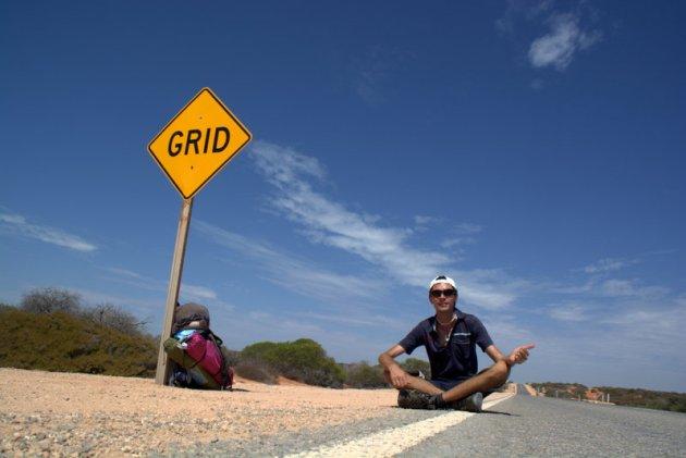 """Czekając na zbawiennego """"stopa"""" pośrodku pustyni w Australii - jedyny cień daje stojący przy drodze znak"""
